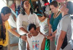 Dann Pantoja, second from left, and his team pray for the pastor of a local church. 'His house was totally destroyed,' says Pantoja. 'His wife and children were hungry when we arrived. Many of his neighbours died. He cannot locate the families belonging to his congregation.' (Photo by Daniel Byron 'Bee' Pantoja / From the PBCI website)