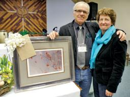 Jim Shantz, pictured with his wife Lorraine, received a Bateman print from Mennonite Church Alberta as a token of appreciation for eight and a half years as conference minister. Shantz completes his term on June 30.