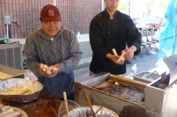 Joung Srithongpan (left) and Max Opas cook spring rolls at Grace Lao Mennonite Church.