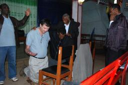 Church leaders pray for Steve Brnjas and Fanosie Legesse (kneeling) before they began their teaching tour in Ethiopia in May.