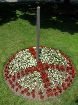 "In 2008, Bethany Mennonite Church in Virgil, Ont., used flowers to put a peace symbol around the church's peace pole. The symbol, first developed for the Campaign for Nuclear Disarmament in England, is made from the semaphore flag signals for the letters ""N"" and ""D,"" standing for nuclear disarmament."